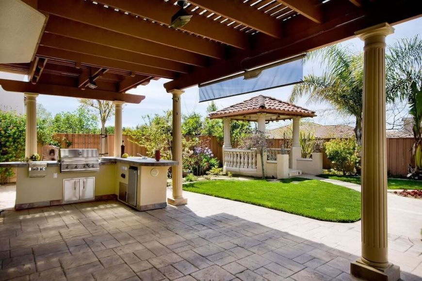 The roof of this gazebo isn't totally solid, but it provides plenty of shade and protection for this stainless steel grill and outdoor cooking area.