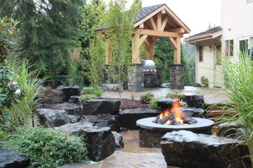 Viewed from the lower fire pit area, the impressive stone and wooden gazebo is a large feature of the heavily landscaped backyard.