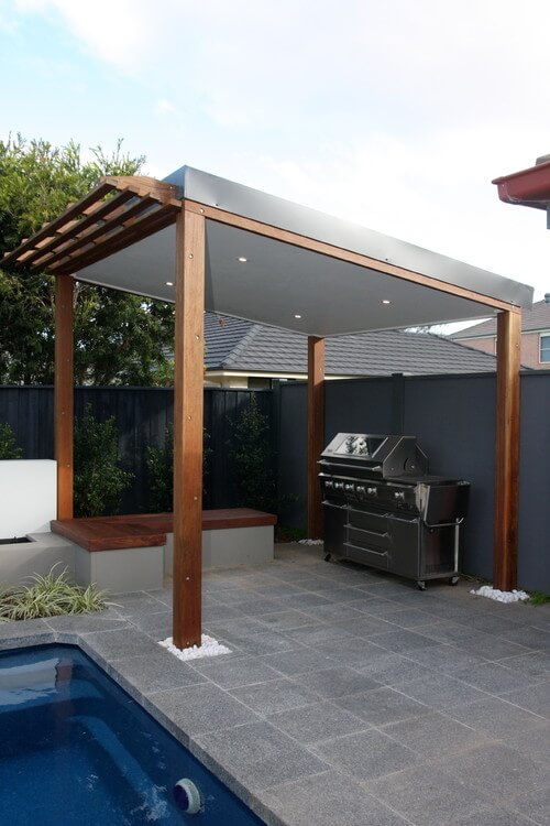 The solid roof of this grill gazebo has a small pergola style overhang near the pool edge, and features an L shaped wooden bench to one side.