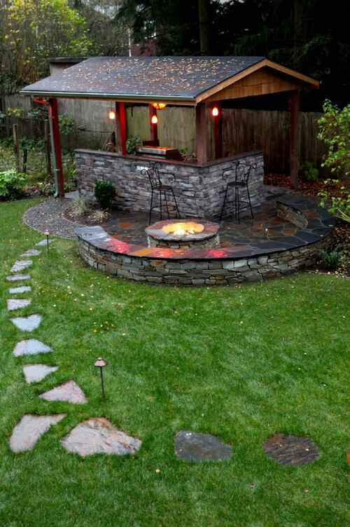 One side of this wood gazebo forms a stone L-shaped bar area. The grill fits snugly into one corner.