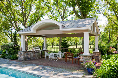This large pavilion covers a grill area, dining table, and a lounge area overlooking a large swimming pool.