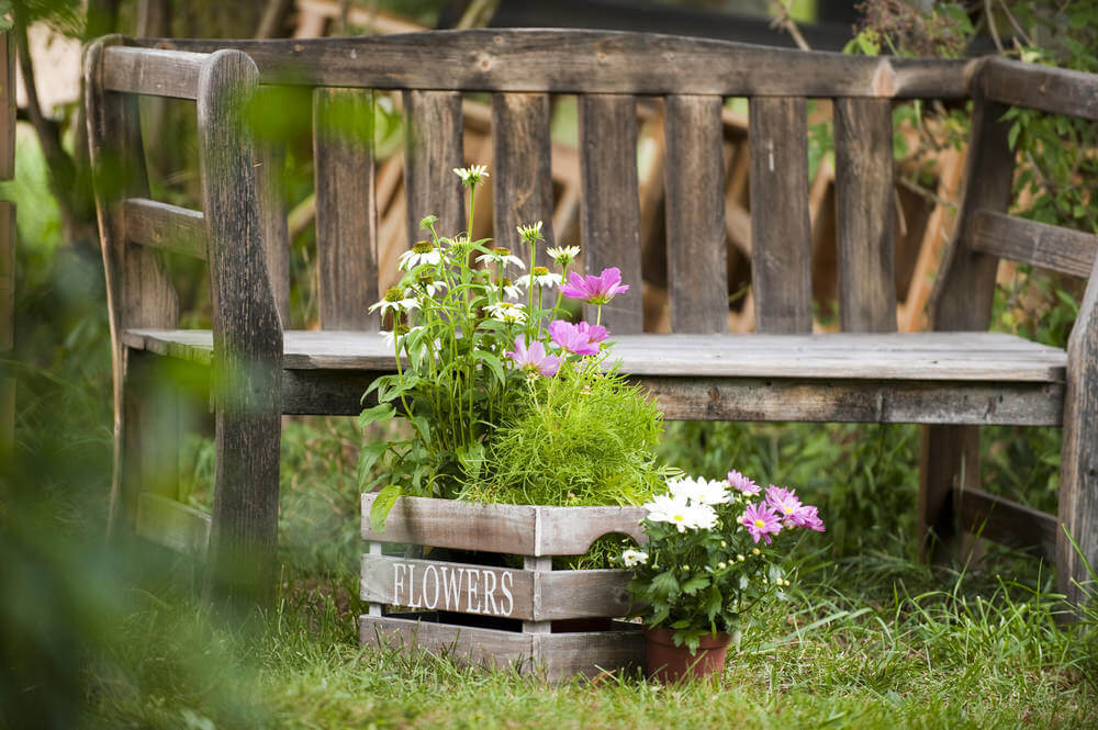 This wooden garden bench and box may have been worn out, soaked in the rain, and broiled on hot sunny days, but the distressedlook makes it more stylish.