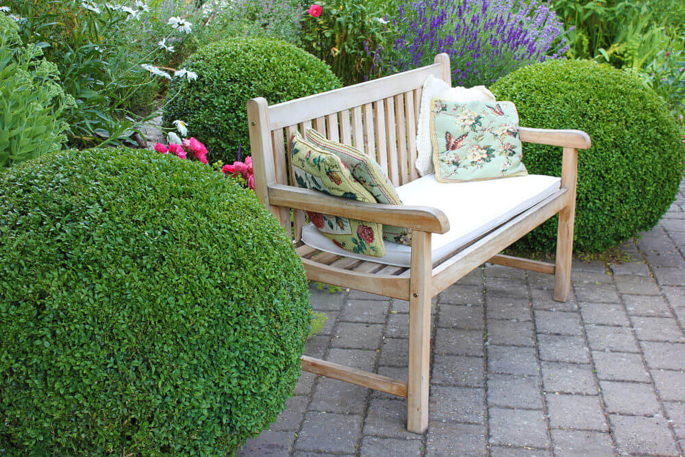 beautiful a wooden garden bench cushioned with floral throw pillows placed in between green topiary and in with garden bench ideas