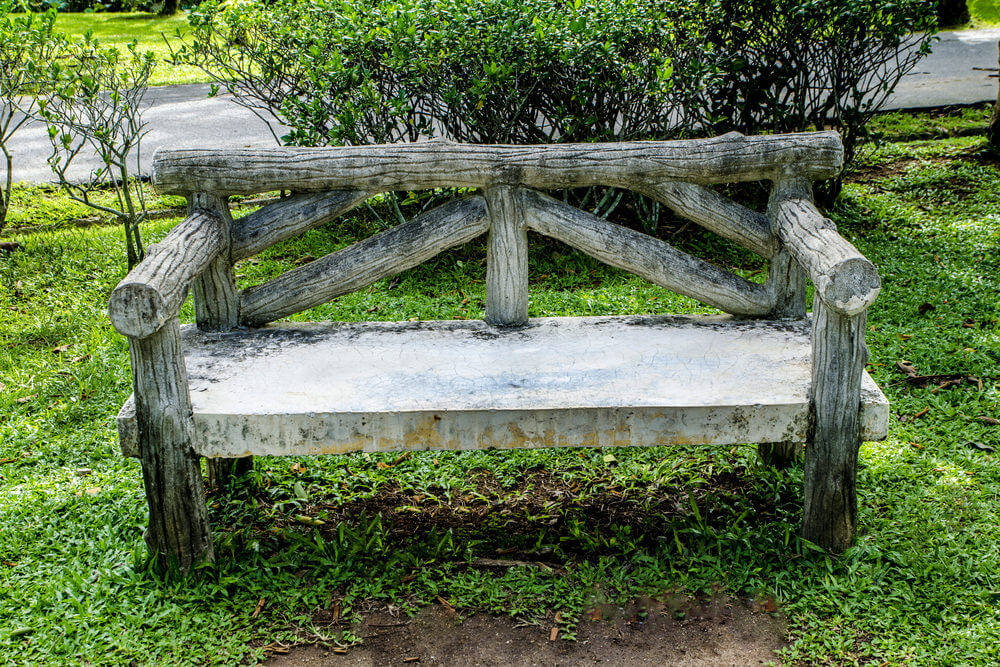 A creative way of displaying a log style garden bench with a more lasting and sturdy concrete seat. Carved logs make up the back rest, arms and support.