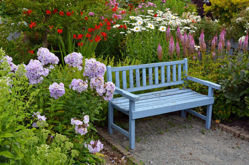 The color of the sky is painted onto this garden bench. It looks very cool surrounded with blossoming flowers in purple, red and white.