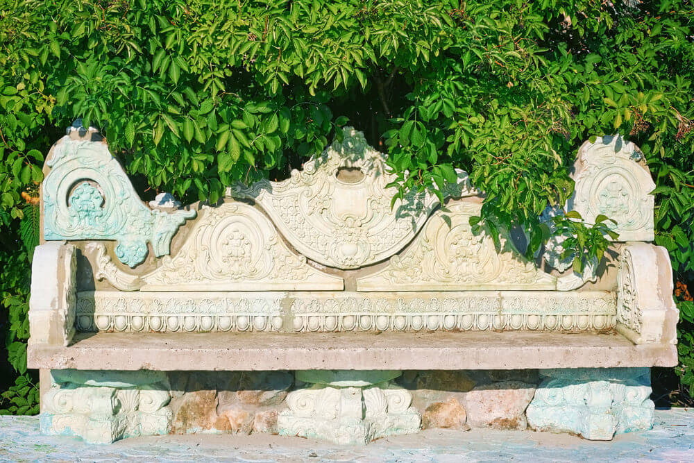 Vintage benches like this one are still fab and trendy despite their antique looks. The carved stone bench has detailed carvings on the back rest and arms.