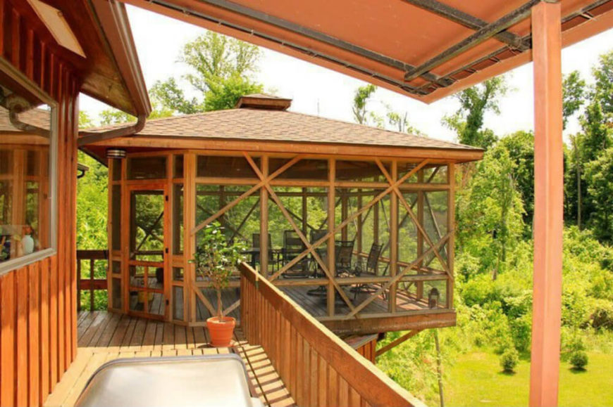 This gazebo hangs over the yard, high above the ground and attached to the deck. The screen walls act as a barrier to insects as well as a way to prevent people from falling off of the gazebo onto the ground below.