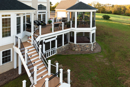 Here is a lovely deckside gazebo with floor to ceiling screens and fences that allow the gazebo to overlook the hillside yard that is behind this home.