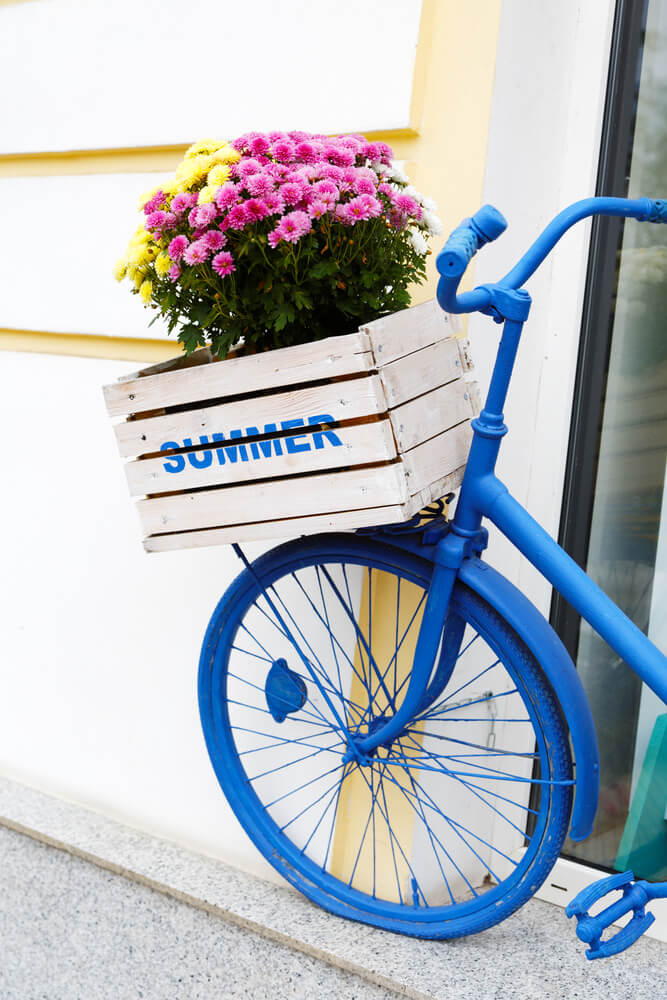 Beach style blue painted bike with white wooden box flower holder on the front.