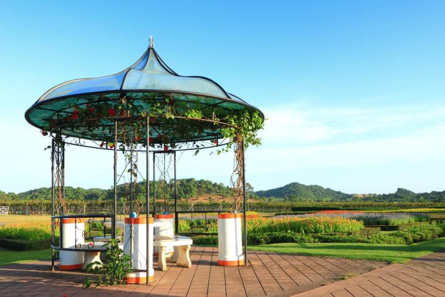 This interesting and dramatic gazebo draws a lot of attention. With a simple metal frame and a striking top, this gazebo houses a great seating area to hang out and watch the day go by.