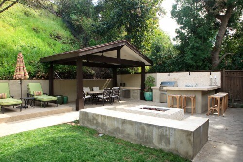 This patio gazebo sits out on a patio near a bar and a grill. Under the gazebo is a wonderful eating area where you and friends can sit and have a fantastic meal in the shade, out of the danger of rain.