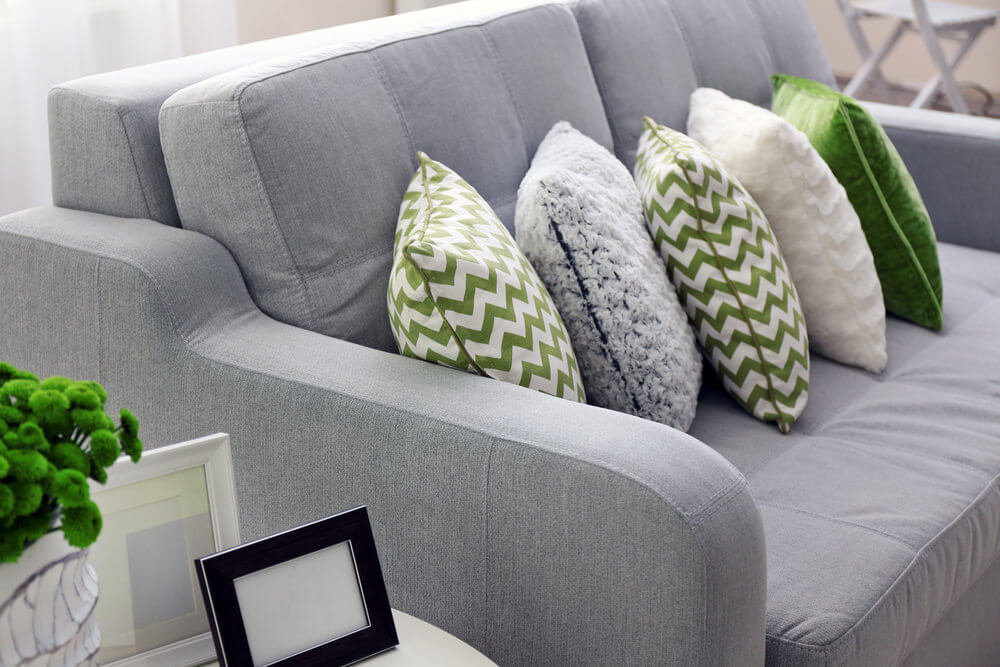 grey sofa with grey white and green throw pillows in an overlapping
