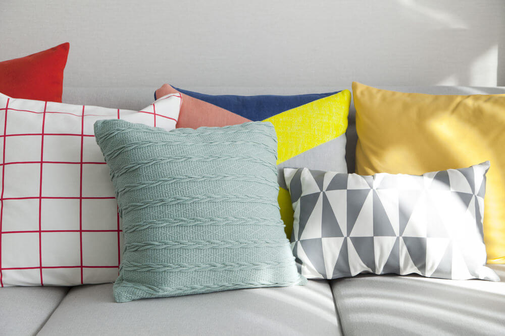 light grey couch with a diverse mix of throw pillows solid and geometric patterns along