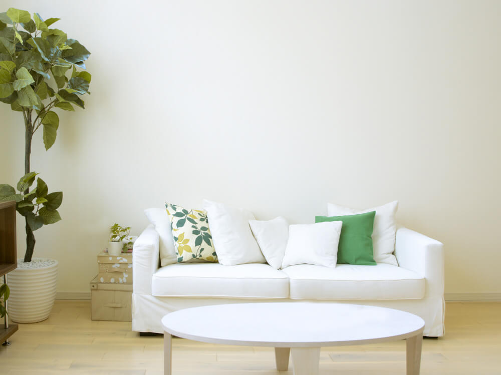 white couch with one floral pillow 5 solid white pillows and one solid green pillow