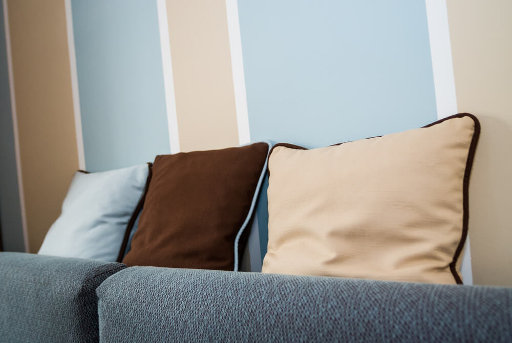 Example of throw pillows integrating with the striped wall colors (blue, white, peach and brown).