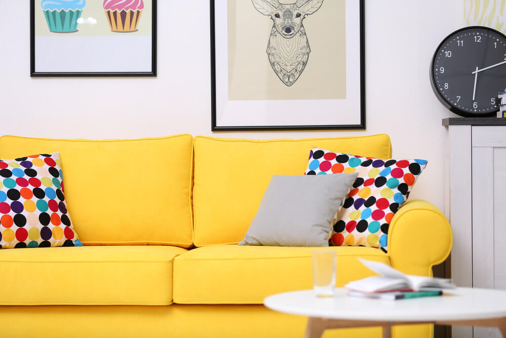 Yellow sofa with brightly colored polka dot throw pillows.