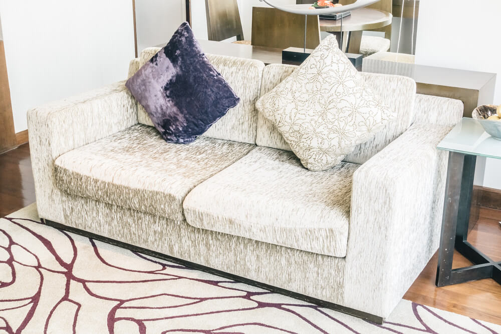 Interesting brushed sofa fabric with matching throw pillow and one purple pillow.
