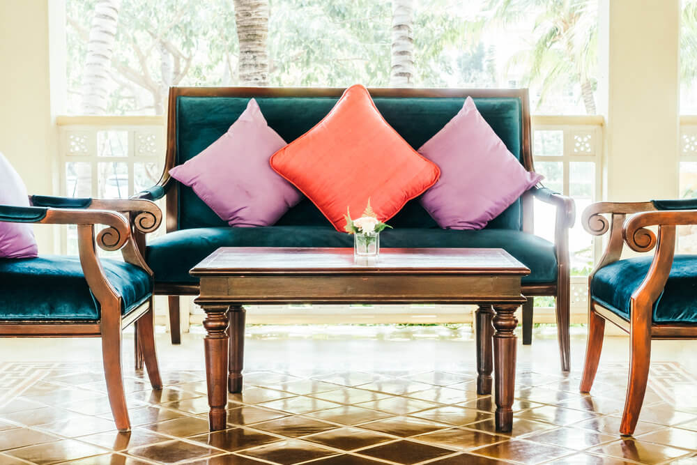 Fussy sofa design reminiscent of a French palace in blue with 2 purple pillows and 1 deep orange throw pillow.