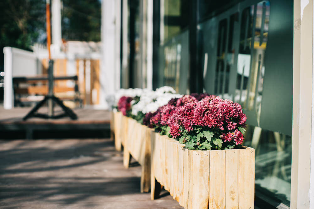 A line of wood planter boxes with flowers lining the edge of a patio. 35 Patio Potted Plant and Flower Ideas  Creative and Lovely Photos