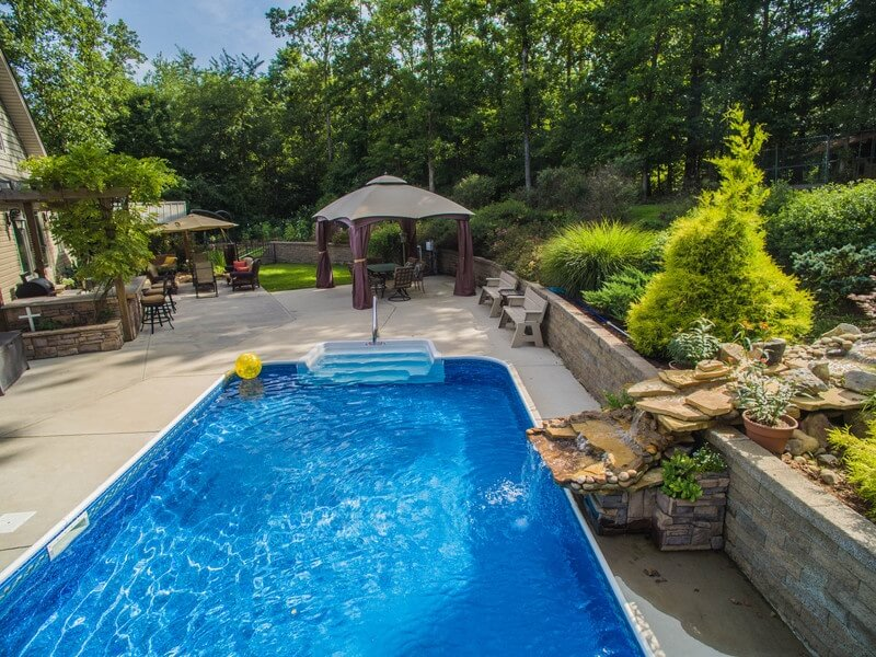 This backyard may have a lot of trees and shade, but a gazebo ensures that as the sun moves through the sky, the shade stays put. It's perfect at the edge of a pool.