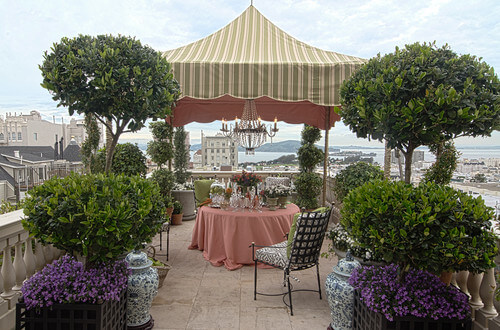 The immensely tall canvas roof of this gazebo has a structure sturdy enough to hang this lovely, elegant chandelier. It transforms this gorgeous balcony into an elegant and comfortable dining area.