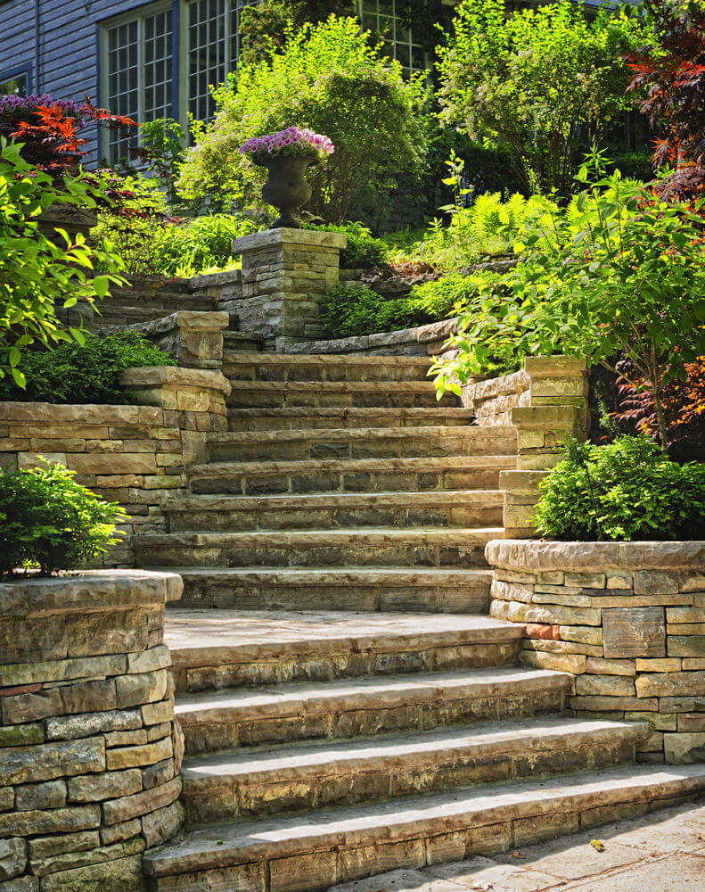 The natural stone steps of a stairway garden feature climb a small - A Large Archaic Vase Of Pink Flowers Stands In The Center Of It All As Stone