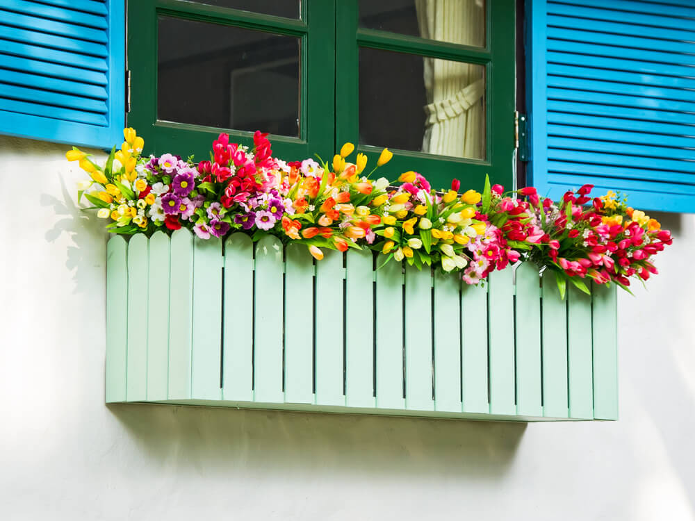 Flower Box Made To Look Like A Picket Fence Overflowing With A Variety Of  Flowers And