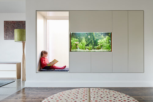This smart reading nook makes use of some space that may have been overlooked otherwise. This little cubby next to the fish tank gives the kids a great space to escape into their stories.