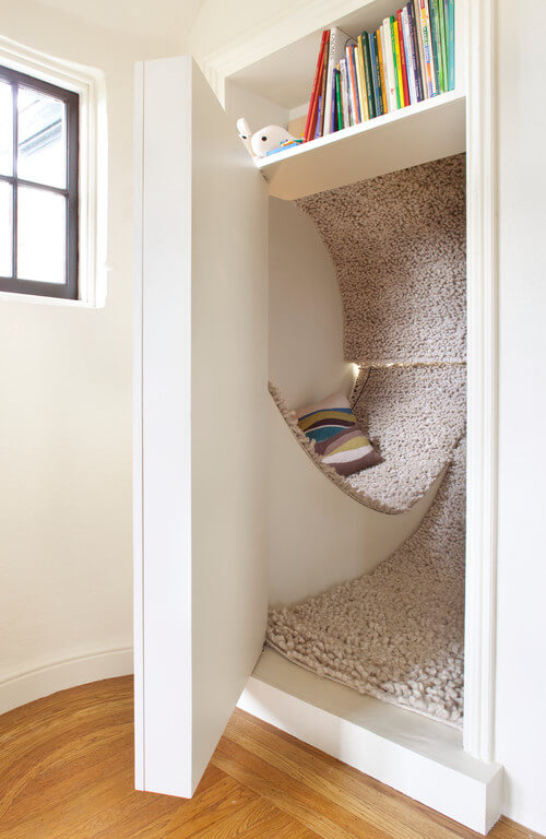 This tucked away spot has a carpeted finish and a door that can close it off when not in use. The space may be small, but it is a perfect place to curl up with a book.
