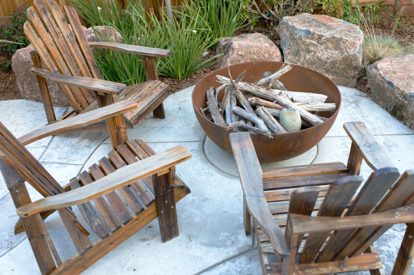 large metal bowl placed on cement patio serving as a small woodburning fire pit