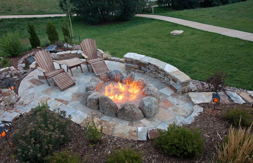 patio with large fire pit created with a series of huge boulders