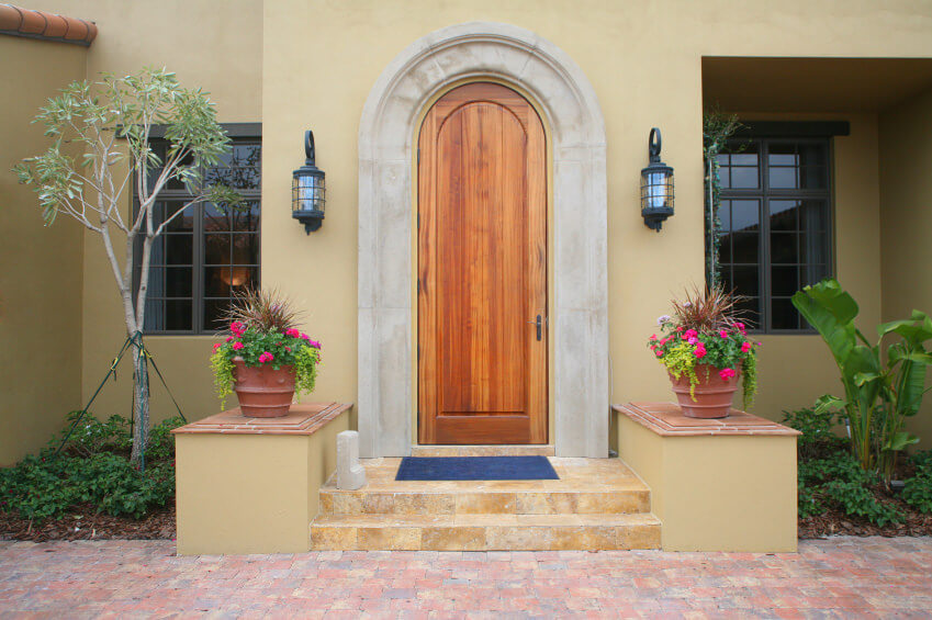 A pair of garden pots with ornamental grasses, strings of pearls and flowers on them, are resting at the front door feeling like they are the attractive ones. There is also a tree and an ornamental banana plant on both sides.