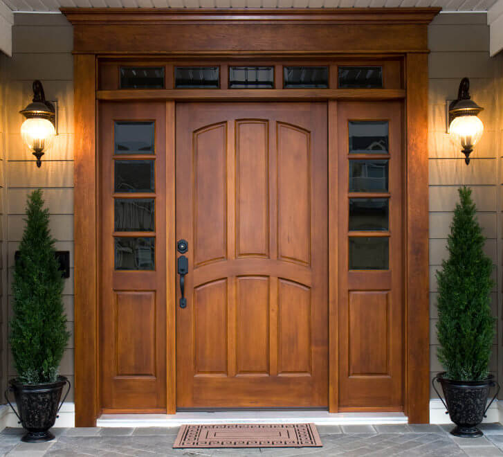 Potted cone shaped pine trees standing symmetrically for a simple yet brilliant looking front door.