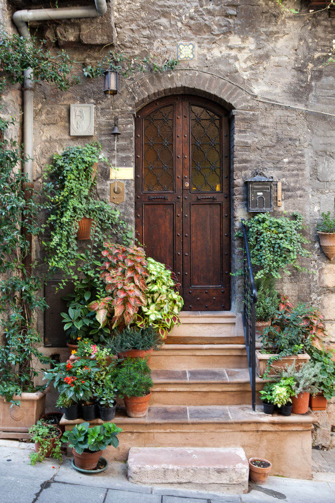 Pots and hanging planters with mayana and other ornamental plants rest on the doorsteps.