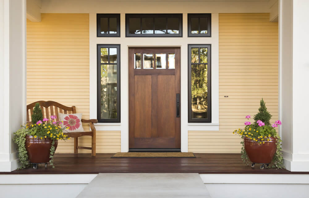 Located right on the porch's side corners are wheeled ceramic pots that home a variety of ornamental plants like daisies, miniature evergreens, geraniums and vine plants.