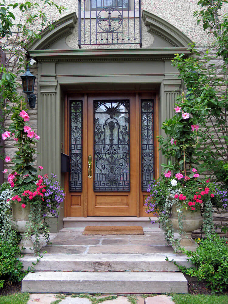 Flowering vines and colorful blossoms in a pair of decorative pots for a symmetrical looking front door.