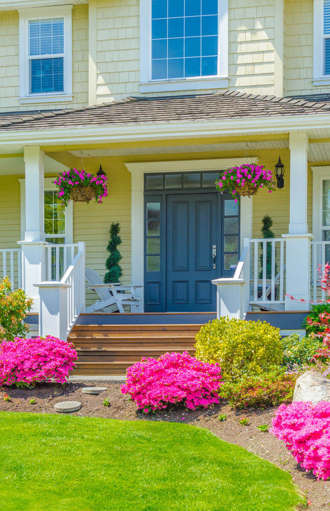A pair of spiral topiary and hanging planters with pink pansies provide the porch's decoration while bushes of blooming pansies are flanking on the sandy ground.