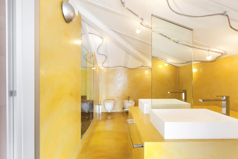 The smoky yellow wall and flooring creates a bright bathroom atmosphere. It's even more striking with the white bathroom sink and ceiling.