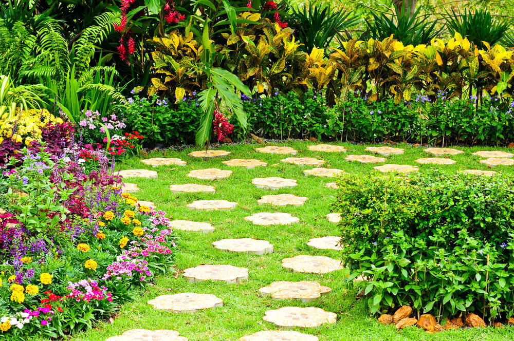 Flower shaped bricks are distributed along the grassy pathway. Curbing along the sides are several flowering plants like marigolds and pansies, added with touches of green, purple and yellow leaves from the shrubs.