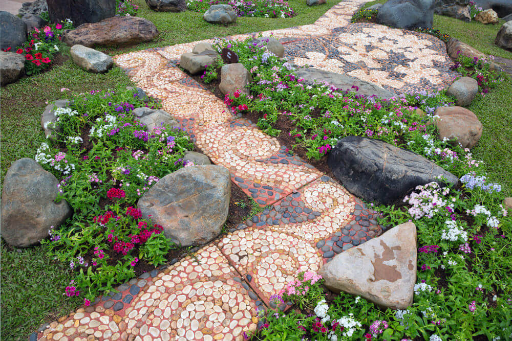 This crooked pathway designed with red concrete and a black and white stone mosaic creates a decorative texture. Medium sized stones are scattered on the sides.
