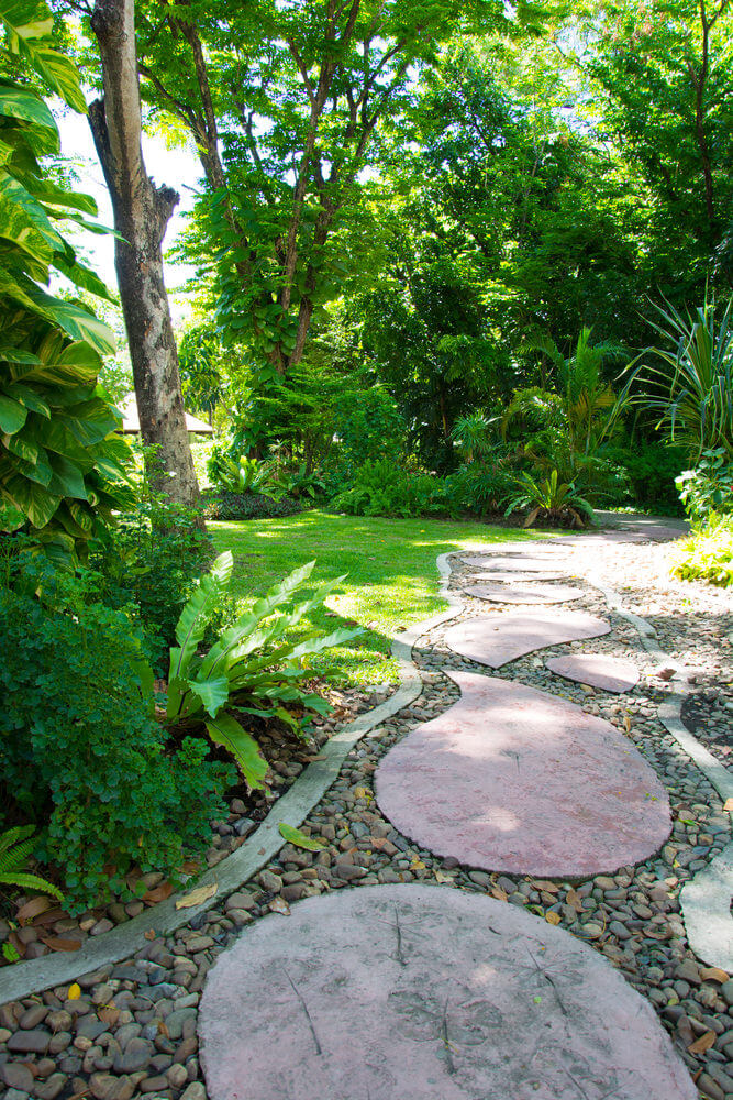 Oval shaped paver with stones and greenery on the corners seem simple and decorative.
