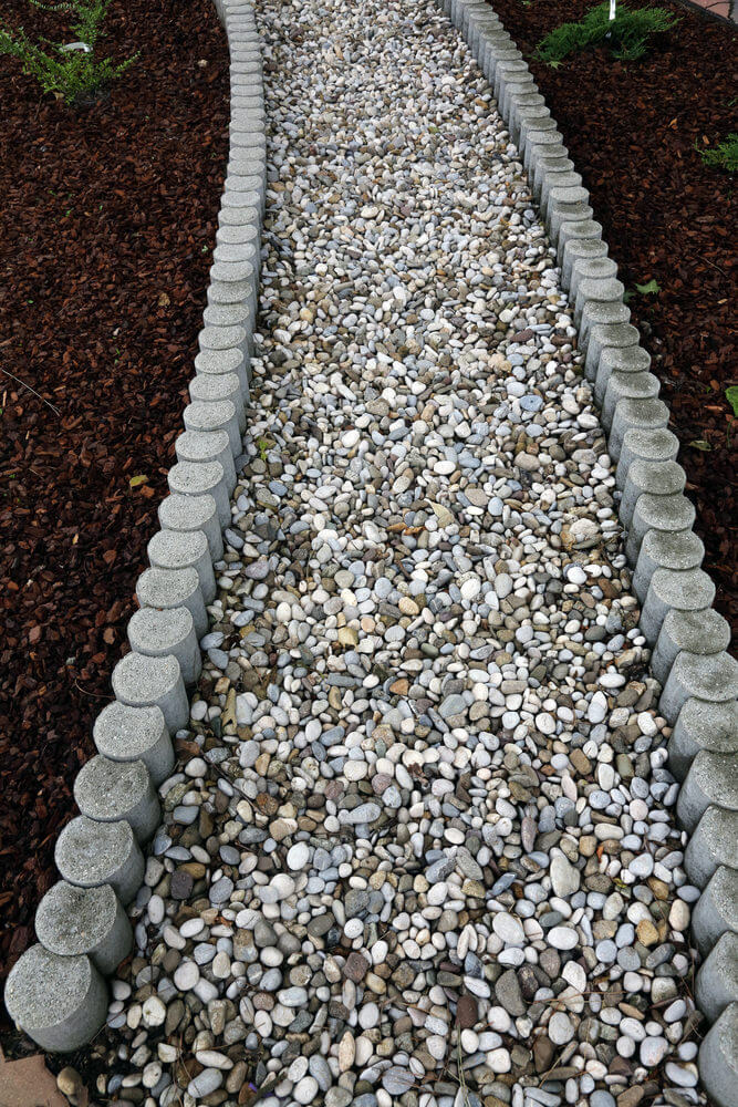 These cylinder curbs stand guard to prevent and protect the pebbles from falling off the pathway.