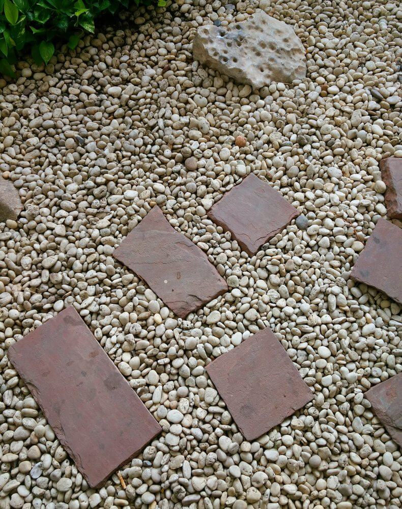 White pebbles with brick stones cut into halves while some remain in full shape.
