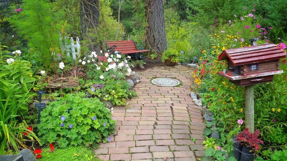 This pathway made of clay brick stones is ornamented with plants, a bird house and a wooden bench on the side.