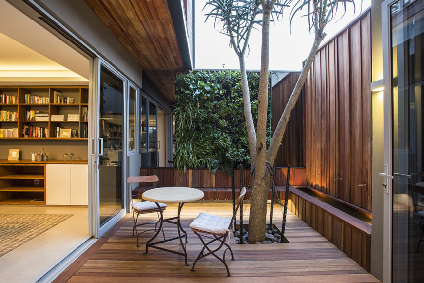 Many rooms throughout the home connect directly to the deck, including this cozy, private space with a tree growing through it. Glass panels and large door openings blur the lines between indoors and out.