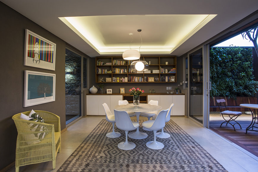 Here's the cozy dining space just inside from the patio seen above. The room is flush with artwork, shelving, and innovative lighting tucked into the raised ceiling.