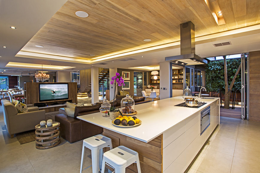 The kitchen sits within a vast open space area, defined by its large island and use of bright natural wood tones. The island features a built-in oven, range, sink, and space for dining.