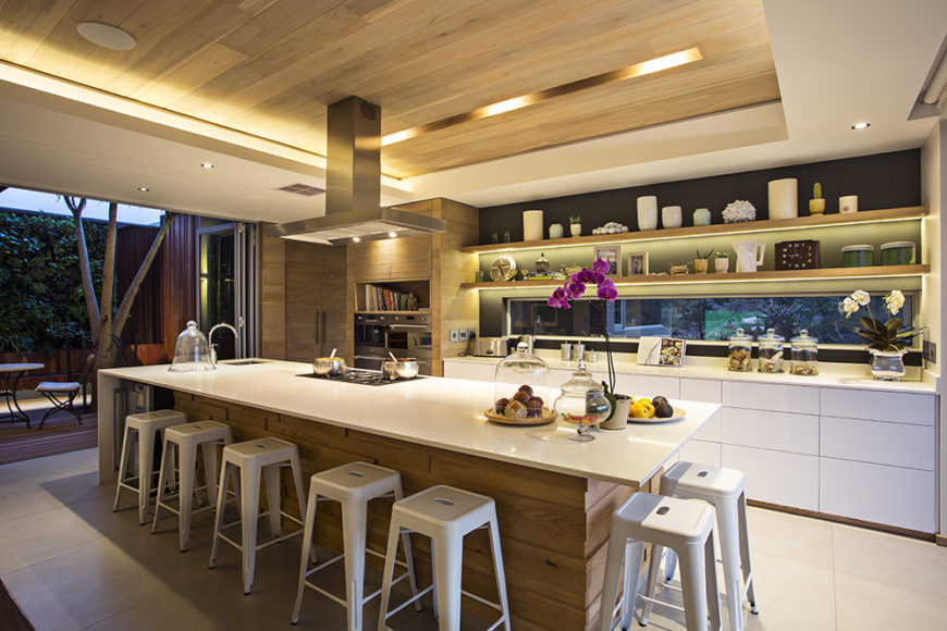 The kitchen also boasts sleek, hardware-less white cabinetry and intricate built-in shelving. The natural wood panels wrap the island, pantry to the left, and span the ceiling.
