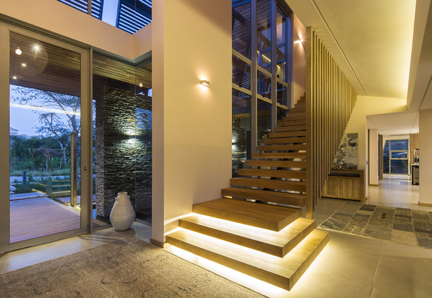 Here at the main entry to th ehome, we see open design staircase leading toward the bedroom areas, with built-in lighting beneath the steps. The front entry is all steel and glass, framed in stone.