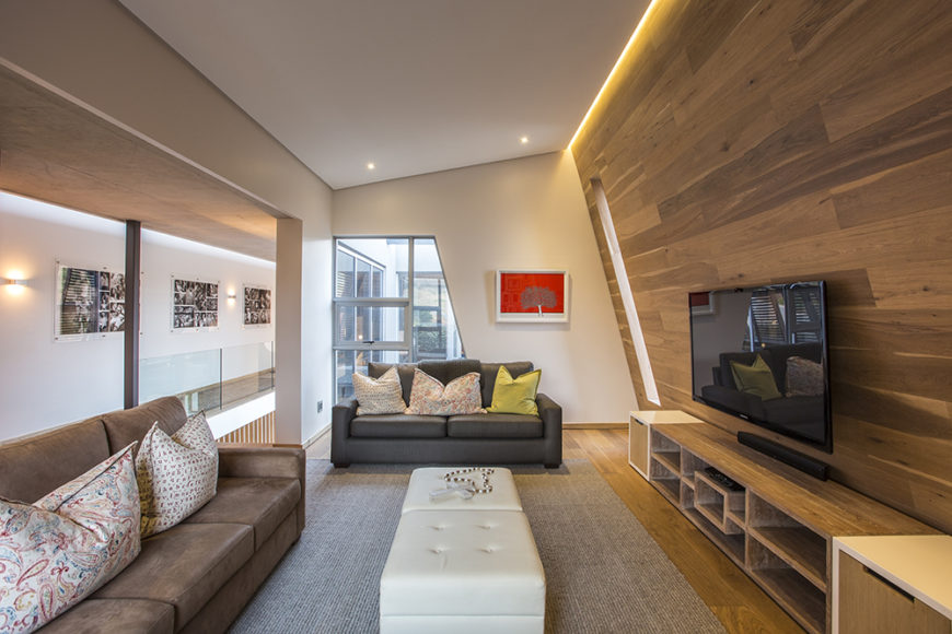 On the upper floor, we see an angular-shaped smaller living room area that flanks the entry space. Here, sleek wood paneling covers the wall and floors, while broad openings allow for views outdoors and throughout the interior of the home.